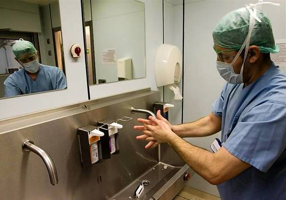 A surgeon washes his hands before starting procedures to clean the wound of an amputee patient with MRSA at Unfallkrankenhaus Berlin hospital