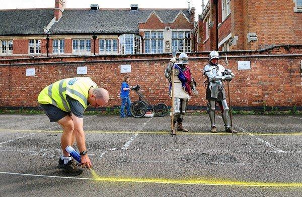Claire Graham uses ground penetration radar at a government parking lot in Leicester, England, as actors dressed as knights look on during the search for the remains of the infamous Richard III.