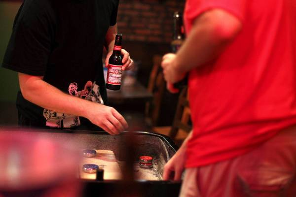 College students play a game of shuffleboard at a Taylor Street bar near UIC. Binge drinking among the collegiate set has been stuck at about 40 percent for most of a decade.