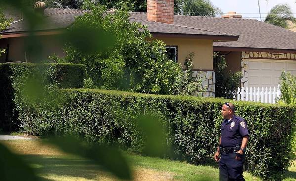 A police officer walks past the house in Riverside where a mother and her two children were stabbed to death last week.