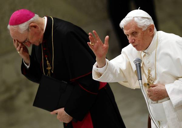 Pope Benedict XVI gives a blessing as he is flanked by bishop James Harvey during a weekly audience at the Paul VI hall in Vatican City.