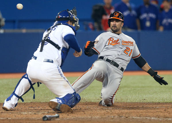 Baltimore Orioles right fielder Nick Markakis (21) slides home safely in the seventh inning as Toronto Blue Jays catcher Jeff Mathis (6) cannot hold onto the ball at the Rogers Centre.