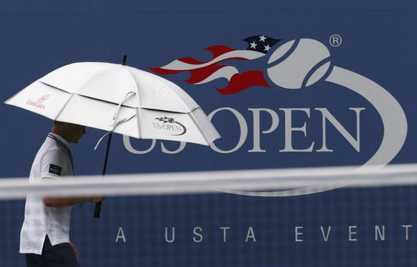 A member of the ground crew walks past a U.S. Open signage during a rain delay at the tennis tournament in New York.