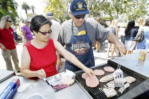 Vietnam War veteran Bill Siddall, center, grills yellowtail fish he caught down in Cabo San Lucas, as his wife Grace, left, lays out beef paddies during an annual Labor Day picnic hosted by the American Legion Post 133 on Monday.