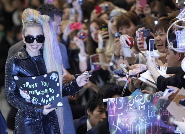 Lady Gaga reacts as she signs autographs for fans upon her arrival at Narita international airport in Narita, east of Tokyo May 8, 2012.