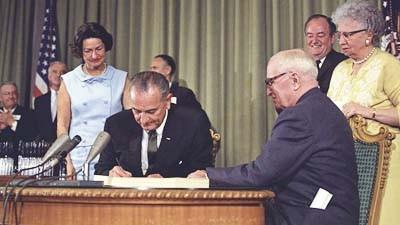President Lyndon B. Johnson signing the Medicare Bill at the Harry S. Truman Library in Independence, Missouri. Former President Harry S. Truman is seated at the table with President Johnson. The following are in the background (from left to right): Senator Edward V. Long, an unidentified man, Lady Bird Johnson, Senator Mike Mansfield, Vice President Hubert Humphrey, and Bess Truman.