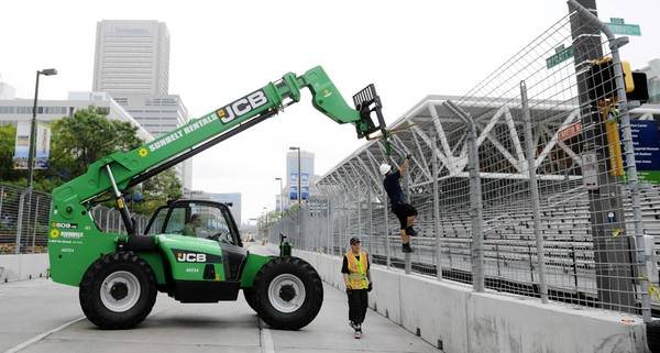 Workers from Conder Inc. of Baltimore take down fences related to the Grand Prix race. Left to right: Brian Tweedale (inside forklift), Ron Sitterly, Ray Gavriszeski (climbing fence.) They are working along Pratt Street near the intersection with Howard Street.