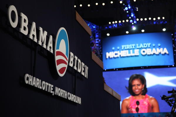 "Inside the Democratic National Convention hall Tuesday night, First Lady Michelle Obama made a sometimes emotional speech on family, women's rights and raising children in the White House, while urging support for another term for President Barack Obama. ""Today, after so many struggles and triumphs and moments that have tested my husband in ways I never could have imagined, I have seen firsthand that being president doesn't change who you are - it reveals who you are,"" she said in her speech, which closed the first night of the three-day convention in Charlotte, North Carolina."