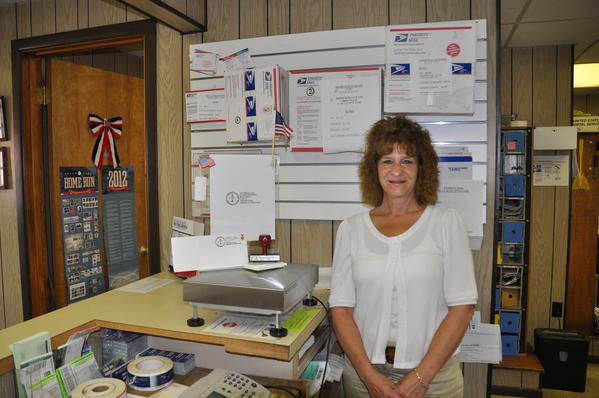 Shanksville post office officer-in-charge Terri Mulhollen stands beside an example of the Flight 93 cancellation stamp.