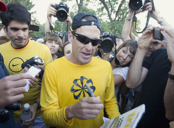 Lance Armstrong signs autographs after a run with fans at Mount Royal park in Montreal on Aug. 29.