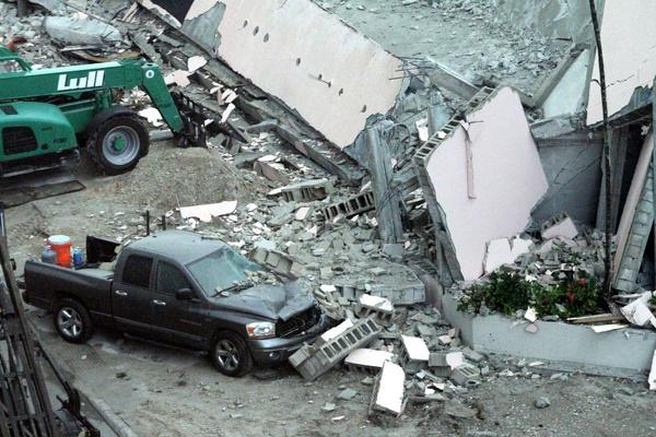 A large piece of a demolished building fell onto this gray pick-up truck, parked next to the building is on the north side of NE 6th Street just west of the Broward County Courthouse.