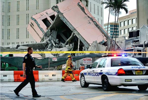 Police and fire personnel walk by the collapsed courthouse parking garage in Fort Lauderdale