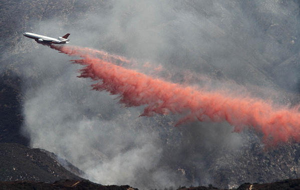 A DC-10 flies through a smoky valley and dumps a load of fire retardant on the Williams fire.