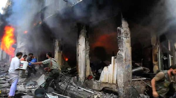 Syrian men are seen on video trying to douse flames in Aleppo's Myasar neighborhood. Government jets have pounded Aleppo daily.