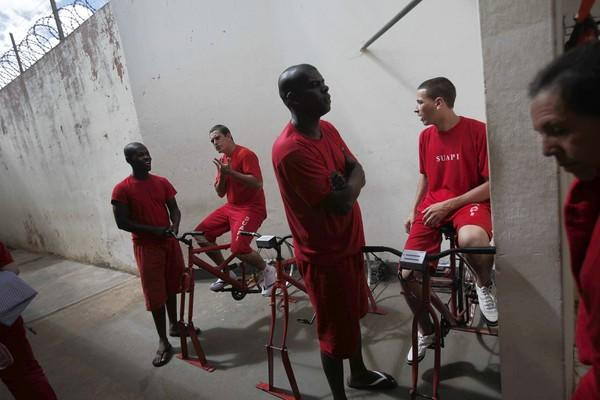 Inmates gather in the area where bicycles are hooked up to generate electricity at the prison in Santa Rita do Sapucai, Brazil.