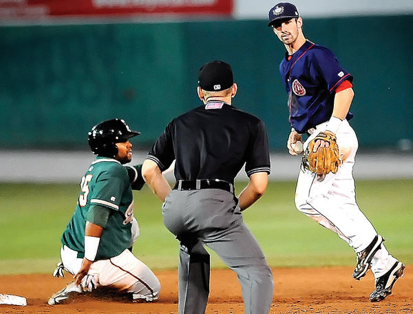 Hagerstown shortstop Bryce Ortega, right, looks for the umpire¿s call after forcing out Greensboro runner Wilfredo Gimenez, left, on a fifth-inning grounder on Wednesday during the Grasshoppers' 3-1 win in the first game of the South Atlantic League Northern Division playoffs.