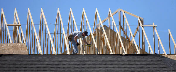 Scott Dreis of Huff Construction takes a measurement as he works on the roof of a hotel under construction near the Lakewood Mall Wednesday. Sunshine and temperatures in the upper 70s made for a good day to be outside. American News Photo by John Davis