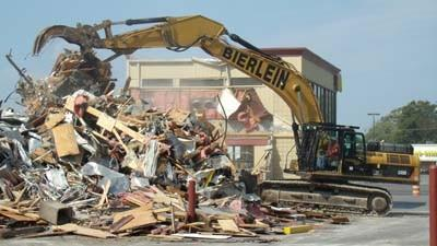 An excavator moves debris Wednesday at the site of Petoskey's McDonald's restaurant on U.S. 31 North, where the main restaurant building had been demolished earlier in the day. McDonald's Corp. and DMR Restaurants, the franchised operator of the fast-food chain's Petoskey location, plan to rebuild the restaurant using a more contemporary design and have it ready to open by mid-fall.