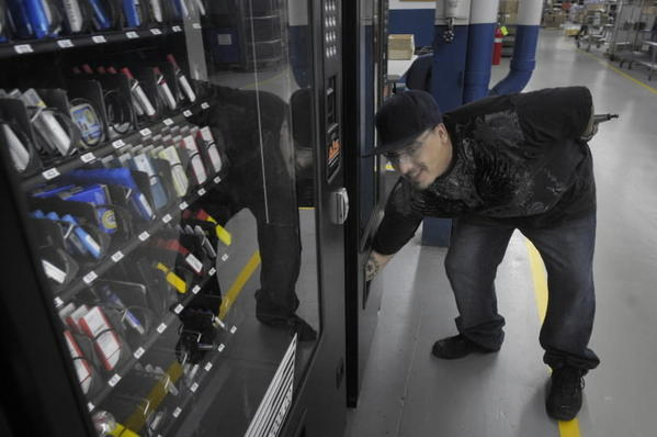 Jorge Velez, of Hartford, reaches for parts after using a vending machine which as a distribution method for dispensing parts.