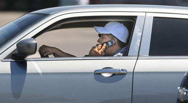 On the eve of a new California law requiring drivers to use hands-free cellphones, a motorist makes use of his handheld phone as he rolls along Rosecrans Avenue in San Diego.