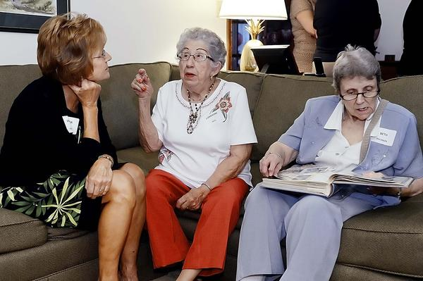 Lorraine Hays, middle, tells Virginia Emerson about her days as a former nurse at Western Maryland State Hospital as Beth Ballinger looks over photos Thursday at a luncheon in Hagerstown.
