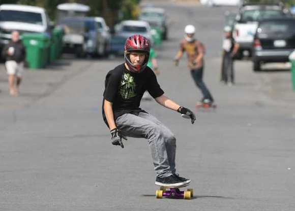 A downhill skateboarder carves down Oak Street during a skateboarding session.