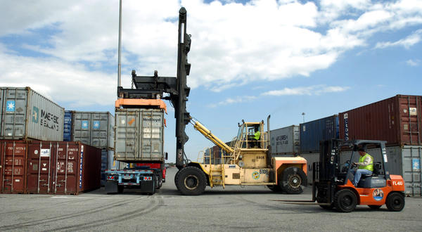 Longshoremen operate equipment to move containers at the Port of Baltimore.