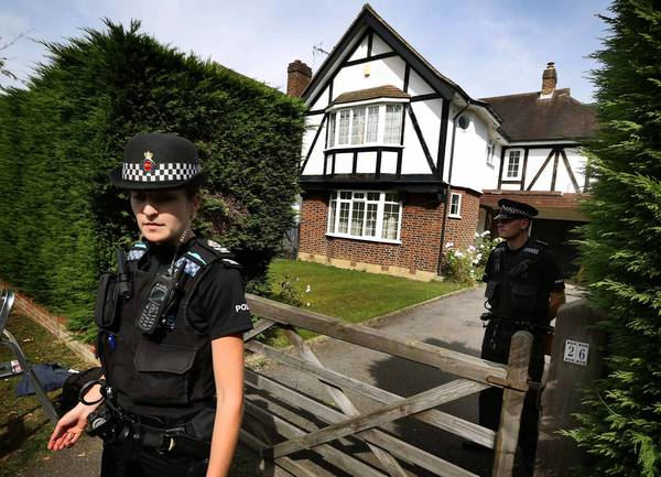 Police are deployed at a home in Surrey, England, said to be the residence of Saad Hilli, the owner of a car in which three people were found shot to death in France.