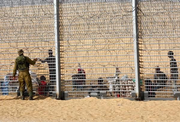 An Israeli soldier hands water to one of the African refugees stranded at the border fence with Egypt.