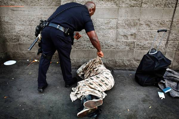 LAPD Officer Deon Joseph tries to wake a man on skid row. Joseph, a nemesis to the beer vendors, says beer and drugs help drive skid row crime.