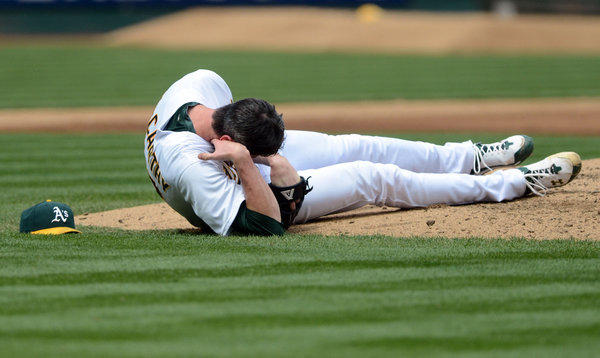 Oakland pitcher Brandon McCarthy holds his head after being hit with a line drive.