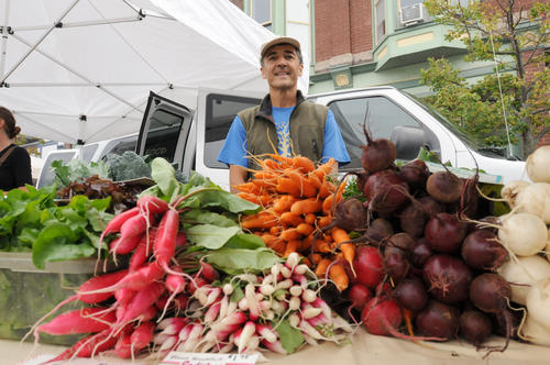 Mike Everts stands behind mountain of fresh vegetables Friday from his farm Blackbird Gardens in Resort Township at the Petoskey farmers market.