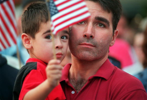 Mike DuBois and his son Brendan DuBois, 3, both of Manchester, listen to Gov. John Rowland deliver an emotional address at a large gathering at the Connecticut House at the Big E in 2001 to honor the victims 9/11 terrorism attract earlier that fall.