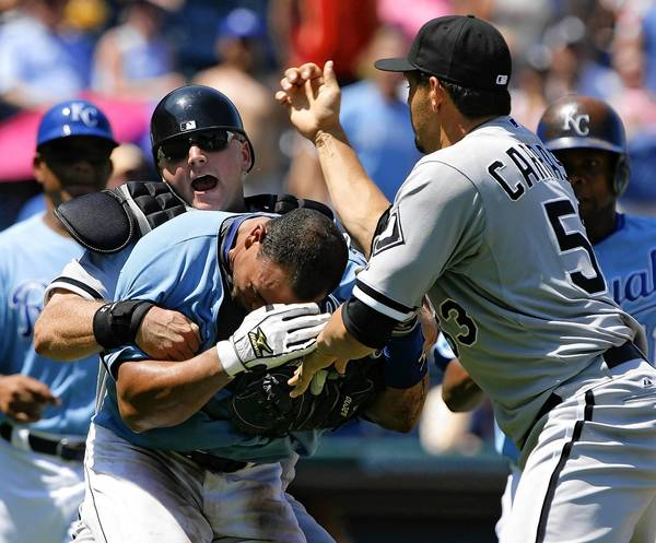 After being hit by a pitch in the fifth inning, Kansas City Royals' Miguel Olivo charges the mound and is grabbed by Chicago White Sox catcher A.J. Pierzynski as relief pitcher D.J. Carrasco meets Olivo at the mound at Kauffman Stadium in Kansas City, Mo.