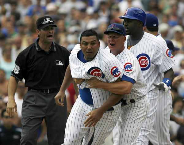 Cubs pitcher Carlos Zambrano, center, is restrained by Cubs third base coach Mike Quade as the benches clear.