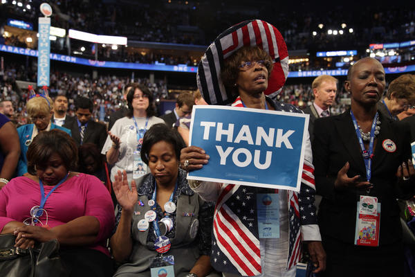 North Carolina delegates, sitting in the front row of the Democratic National Convention, join in the final night's closing prayer with Cardinal Timothy Dolan, the archbishop of New York.