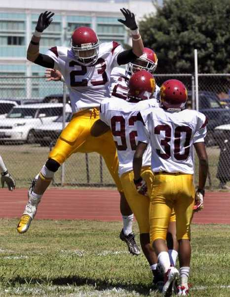 Glendale defensive back Matt Lopez, left, celebrates after intercepting a pass and returning it for a touchdown during Glendale Community College's season opener against El Camino-Compton College.
