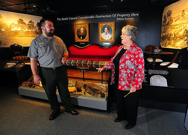 National Park Service ranger Alann Schmidt chats Friday with Suzanne Roulette Nalley at the opening of a new exhibit at Antietam National Battlefield visitor center. Numerous artifacts in the room were donated or are on loan to the Park Service, and came from descendants of farmstead owners at the time of the September 1862 battle in Sharpsburg.