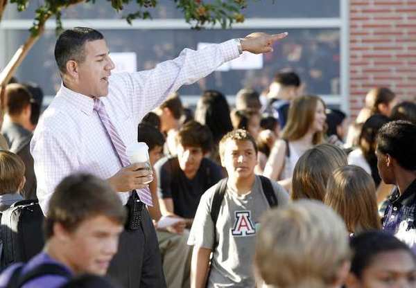 John Burroughs High School Principal John Paramo helps guide students to classrooms while standing on the bench of a picnic table on the first day of school.
