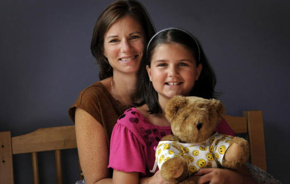 Janice Soviero and her 10-year-old daughter, Elena in Elena's room at their Milford home. Elena had brain surgery in March last year to remove a large clot. Elena is doing fine now and is in the fifth grade. She is hugging a teddy bear wearing a hospital gown given to her by her classmates when she was in the hospital.