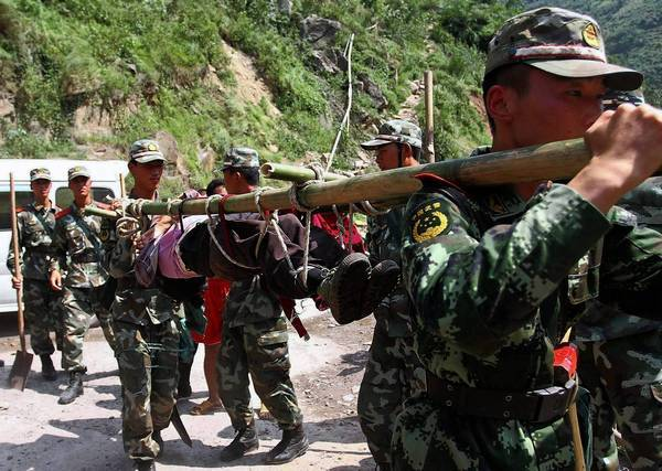 Chinese paramilitary police carry an earthquake victim in Zhaotong, in Yunnan province's Yiliang county.