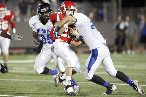 Burroughs' Josh Storer, left, gets tackled by Ilia Petrosyan during a game at John Burroughs High School in Burbank on Friday, September 7, 2012.
