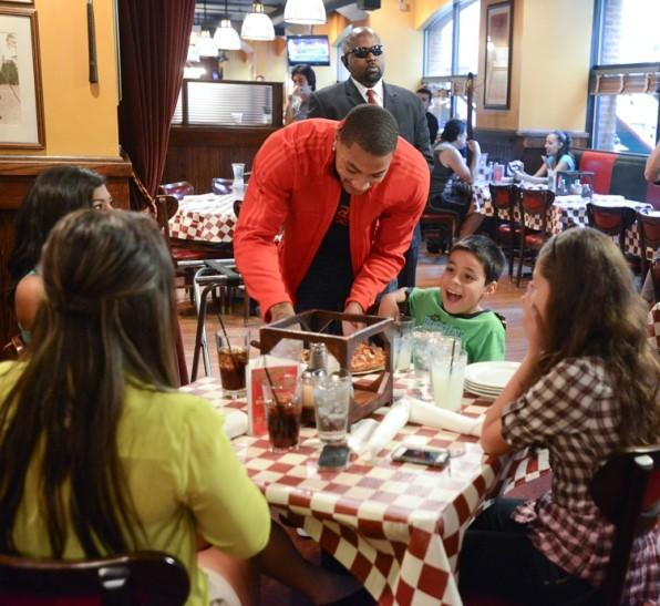 The Bulls' Derrick Rose delivers a pizza to a table at Giordano's on Rush Street September 6, 2012.