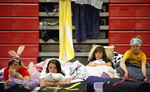 "Hayley Stuber (left), Carla Werich (second left), Amy Martello (third left), and Emma Stibich, listen as Sister Melissa Blankestyn reads to them from a children's book ""If You Give a Mouse a Cookie"" at Center Grove Middle School Central in Greenwood, Ind., where the band spent the night before competing in the semi-finals on Saturday in Indianapolis."