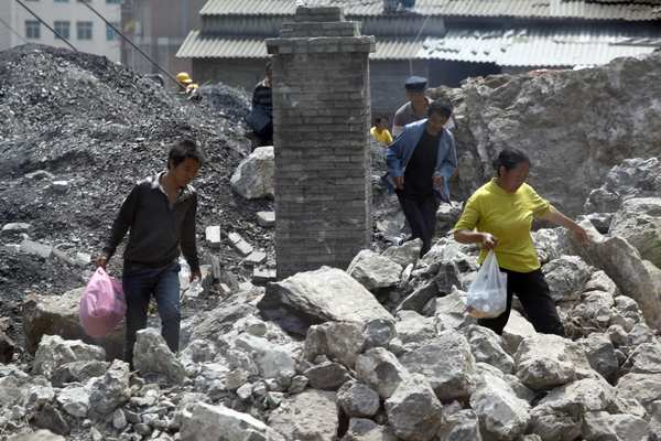 Survivors sift through the remains of a collapsed home in Yiliang in a remote and mountainous area of southwest China. Witnesses said residents ran screaming from their homes and business as two quakes hit on the border of Yunnan and Guizhou provinces an hour apart, followed by a string of aftershocks.