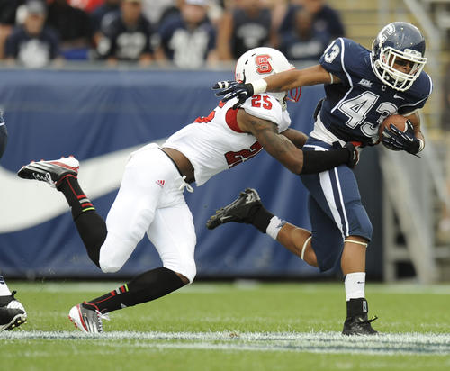 UConn running back Lyle McCombs tries to escape the grasp of NC State's Dontae Johnson at Rentschler Field Saturday.
