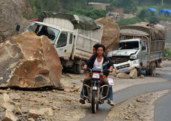 Men ride past damaged vehicles lying by the side of the road after being caught in a landslide after a series of earthquakes hit Yiliang County in southwest China.