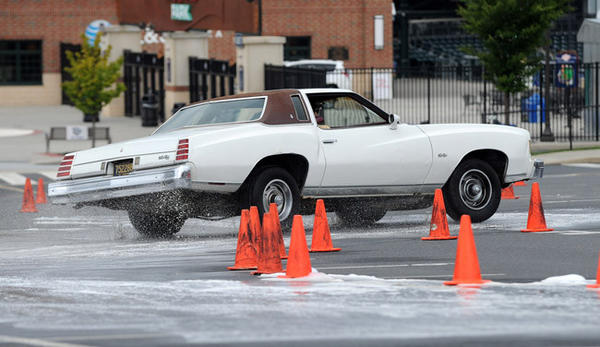 "Josh Gaines, 17, of Newark, Delaware drives on a slippery, soapy mix of detergent and water at high speed. The Sports Car Club of America (SCCA) in conjunction with the Delaware Valley BMW CCA put on a Rack Street Survival event at Coca-Cola Park to give young drivers ""hands-on"" driving experience in real-world situations."