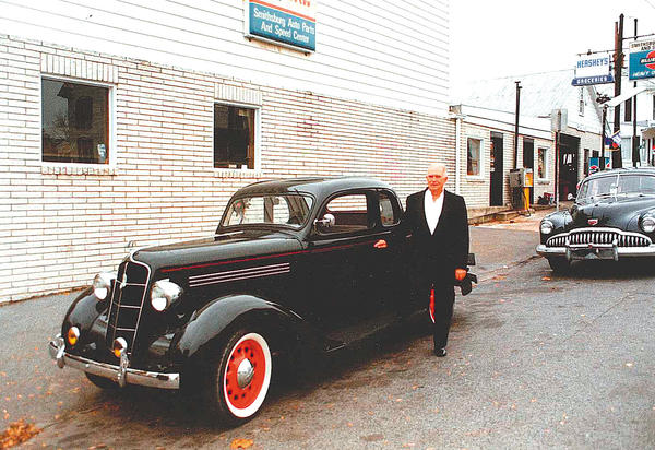 Milt Lawyer stands in front of his business, Smithsburg Auto Body Shop, in 1992, with a 1935 Plymouth, similar to one he previously had owned, and a 1949 Buick behind it. He and youngest son Brian had driven the Plymouth back from Kansas.