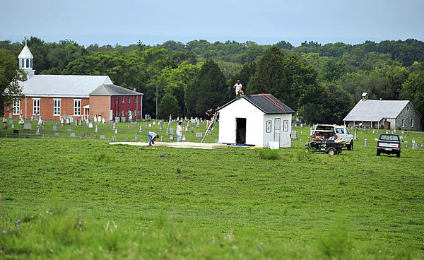 Lloyd Clever of Clear Spring, Bill Coe of Gettysburg, Pa., Joe Forrester of New Freedom, Pa., and Mark Beasley of Williamsort, standing on top of the replica Dunker Church, build and prep landmarks on Legacy Manor Farm in Boonsboro Wednesday for the Battle of Antietam re-enactment.